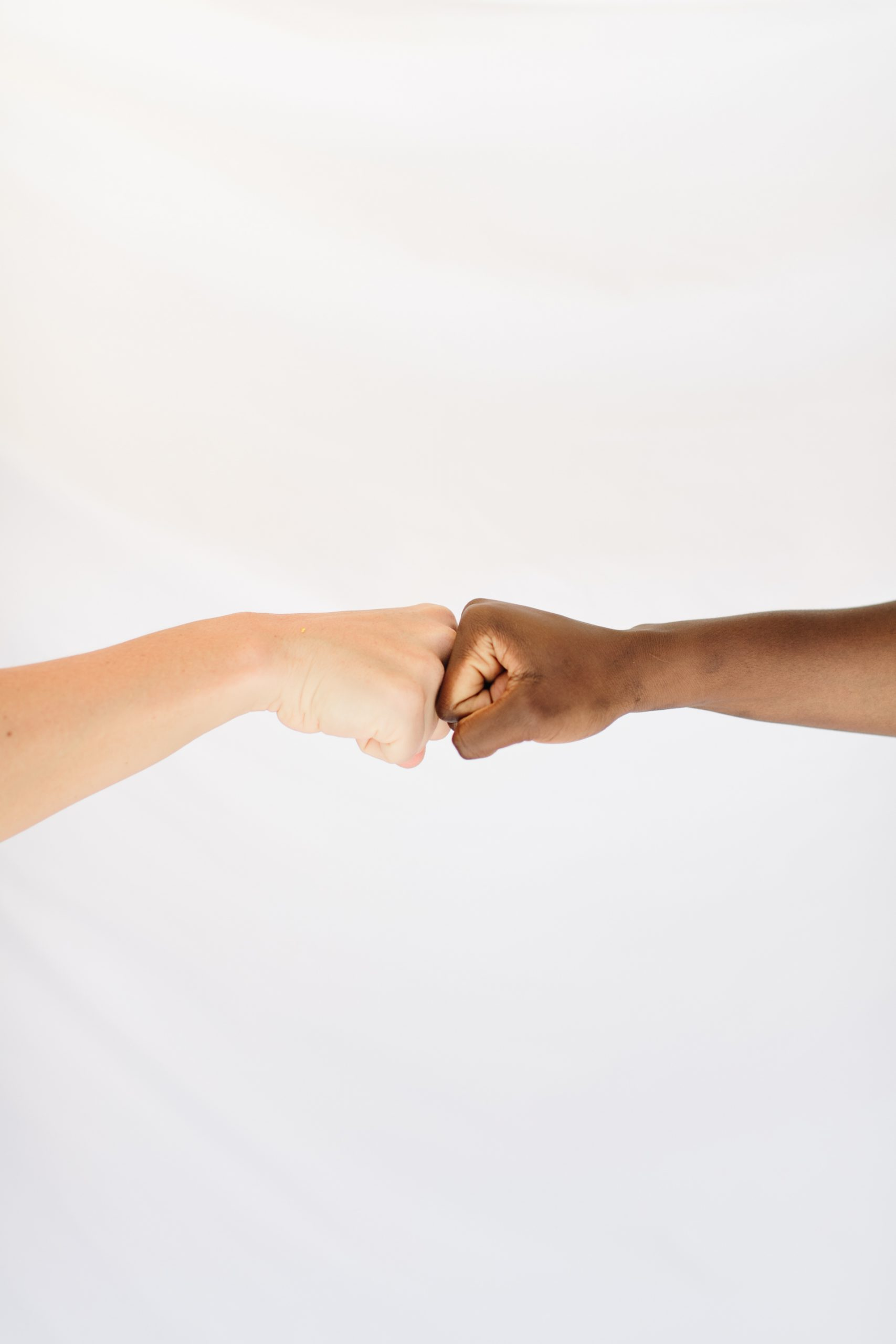 Fist bumping between a white and a black hand